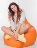 Ładny dziewczyny obsiadanie na pomarańczowej poduszce Obrazy Royalty Free