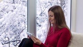 Ładny dziewczyny obsiadanie na windowsill patrzeje okno i używa pastylka komputer z słuchawkami, na zewnątrz zimy zbiory