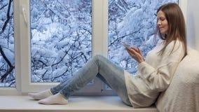 Ładny dziewczyny obsiadanie na windowsill patrzeje okno i używa pastylka komputer, na zewnątrz zimy zbiory wideo