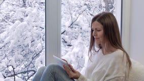 Ładny dziewczyny obsiadanie na windowsill patrzeje okno i używa pastylka komputer, na zewnątrz zimy zbiory