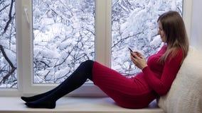 Ładny dziewczyny obsiadanie na windowsill patrzeje okno i używa smartphone, na zewnątrz zimy zdjęcie wideo