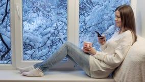 Ładny dziewczyny obsiadanie na windowsill, pić herbacianym i używać smartphone, na zewnątrz zimy zdjęcie wideo