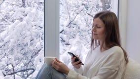 Ładny dziewczyny obsiadanie na windowsill, pić kawowym i używać smartphone, na zewnątrz zimy zbiory wideo