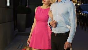 Ładny dziewczyny odprowadzenie i mienie mężczyzna pod ręką, patrzeje butik gablotę wystawową zbiory wideo