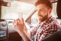 Ładny facet bierze obrazek jego partner na białym telefonie Jest przyglądający ekran i ono uśmiecha się trochę Facetów spojrzenia obrazy stock