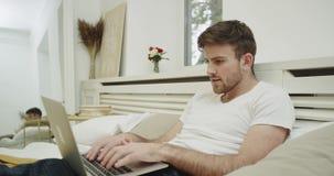 Ładny facet praca czas w jego łóżka być ubranym i używać jego notatnika klapanie piżamy coś na klawiaturze zdjęcie wideo