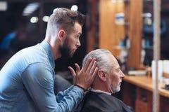 Ładny fachowy fryzjer męski modeluje fryzurę Fotografia Royalty Free