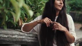 Ładny garbnikujący kobiety czekanie dla someone w parku z henna tatuażami na jej rękach zbiory