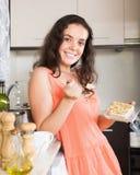 Ładny gospodyni domowej łasowania ciastko w domu Obrazy Royalty Free