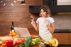 Ładny gospodyni domowej czytanie od jej pić wina i laptopu Zdjęcie Royalty Free
