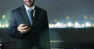 Ładny i młody człowieku używa jego telefon uśmiechnięty i szczęśliwy enjoing jego plan biznesowego zbiory wideo