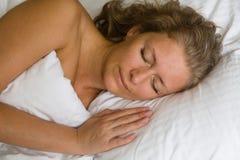 Ładny kobiety dosypianie w łóżku pod pokrywami zdjęcie stock