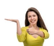 Ładny kobiety przedstawienia kciuk up podpisuje z prawa ręka ono uśmiecha się w yello Obrazy Stock