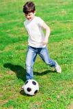 Ładny męski dziecko bawić się futbol na trawie Obrazy Royalty Free