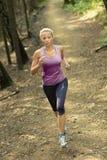 Ładny młoda dziewczyna biegacz w lesie Obrazy Stock