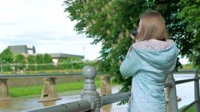 Ładny młoda dziewczyna fotografa turysta bierze fotografie z fachową kamerą blisko poręcza na nabrzeżu, rzeka zbiory