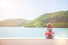 Ładny młoda kobieta turysta siedzi na halnym jeziorze na słonecznym dniu dziewczyna patrzeje w pięknej odległości Widok od plecy obraz stock