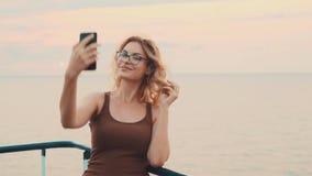 Ładny młodej dziewczyny blogger bierze jej podróż na kamerze, dama z blondynem i szkła robią selfie dla jej rodziny zdjęcie wideo