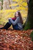 Ładny młodej dziewczyny obsiadanie na wysuszonych liściach w lesie Fotografia Royalty Free