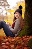 Ładny młodej dziewczyny obsiadanie przeciw drzewu w jesieni Zdjęcia Stock