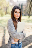 Ładny młodej kobiety odprowadzenie z laptopem pod ręką w parku Obraz Stock