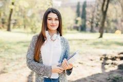 Ładny młodej kobiety odprowadzenie z laptopem pod ręką w parku Zdjęcia Stock