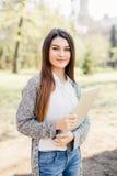 Ładny młodej kobiety odprowadzenie z laptopem pod ręką w parku Zdjęcie Stock