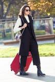 Ładny młodej kobiety odprowadzenie z walizką dworzec zdjęcie royalty free