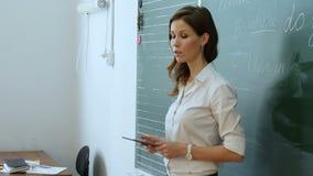 Ładny młody żeński nauczyciel mówi coś z pastylką w ona ręki zbiory wideo