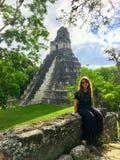 Ładny młody żeński turysta pozuje przed Tikal ruinami, antyczne Majskie ruiny w tropikalnych lasach deszczowych północny Gwatemal obraz royalty free