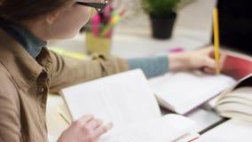Ładny młody żeński uczeń pisze w notatniku podczas gdy czytający zbiory