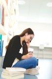 Ładny młody żeńskiego ucznia siedzący studiowanie obraz royalty free