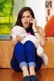 Ładny młody brunetki kobiety mienia brzemienności domu test opowiada na telefonie i patrzeje szokujący, teddybear w podołku, ogró Obraz Royalty Free