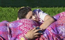Ładny młody chłopiec lying on the beach na jej mum's brzuchu w parku obrazy royalty free