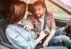Ładny młody człowiek blokuje jego seatbelt i patrzeje dziewczyny która robi ten sam rzeczy Jest przyglądająca on ludzie obrazy stock