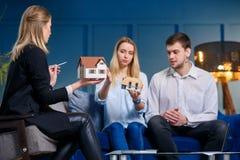 Ładny młody człowiek i kobieta dyskutuje projekt dom z młodym żeńskim projektantem w błękitnym biurze zdjęcie royalty free
