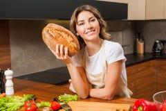 Ładny młody gospodyni domowej mienia chleb w ona ręki Zdjęcia Stock