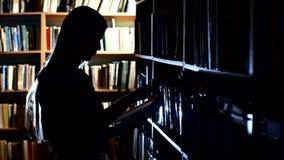 Ładny młody student collegu w bibliotece, wybiera zbiory