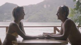 Ładny młody szczęśliwy pary obsiadanie opowiada i trzyma, wręcza each inny stołem podczas ich wakacje zdjęcie wideo