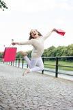 Ładny małej dziewczynki doskakiwanie na ulicie z różowymi torba na zakupy Fotografia Royalty Free
