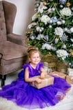 Ładny małej dziewczynki 4 lat w błękitnej sukni Dziecko w Bożenarodzeniowym pokoju z teddybear, dużym zegarem, choinka, brązu kar zdjęcie royalty free