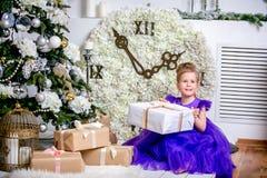 Ładny małej dziewczynki 4 lat w błękitnej sukni Dziecko w Bożenarodzeniowym pokoju z teddybear, dużym zegarem, choinka, brązu kar zdjęcia royalty free