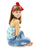 Ładny małej dziewczynki obsiadanie na podłoga w cajgach Zdjęcia Stock