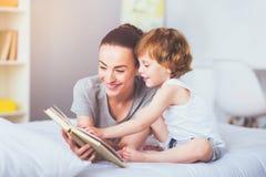 Ładny macierzysty czytanie książka jej uroczy syn Zdjęcia Stock