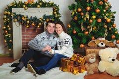 Ładny miłości pary obsiadanie na dywanie przed grabą Fotografia Stock