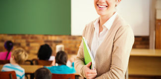 Ładny nauczyciel ono uśmiecha się przy kamerą przy plecy sala lekcyjna Zdjęcia Royalty Free