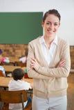 Ładny nauczyciel ono uśmiecha się przy kamerą przy plecy sala lekcyjna Obrazy Stock