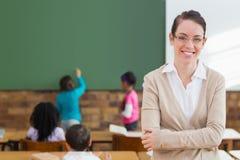 Ładny nauczyciel ono uśmiecha się przy kamerą przy plecy sala lekcyjna Zdjęcia Stock