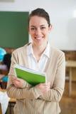 Ładny nauczyciel ono uśmiecha się przy kamerą przy plecy sala lekcyjna Obraz Royalty Free