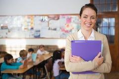 Ładny nauczyciel ono uśmiecha się przy kamerą przy plecy sala lekcyjna Zdjęcie Stock